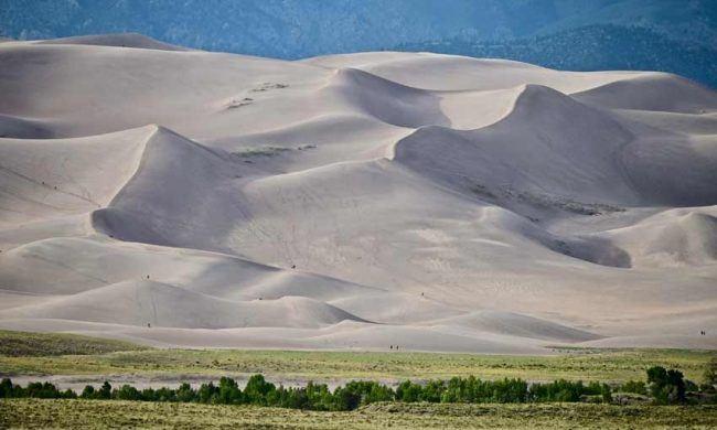 A seasonal river popular with families runs through the dunes.
